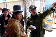 A policeman shows an Aymara woman where to vote.