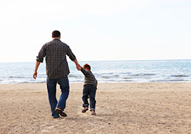 Photo from behind of a man and young son holding hands, walking on a beach.