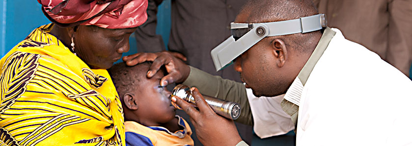Mother holds her child who is receiving and eye exam.