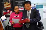 Christine Yuan and Cong Riyun complete the observer checklist as polls open in Falls Church, Va.