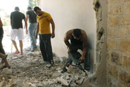 Friends help the Sa'id family demolish the second floor of their home.