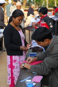 a woman presents her identification card before voting in Nepal.