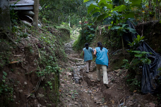 Two health workers walk through the Guatemalan jungle.