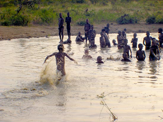 Children swim in a shallow pond in Nigeria.