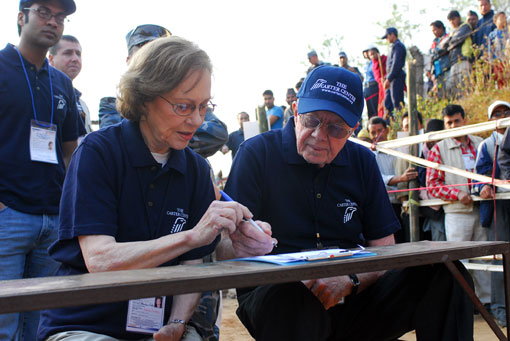Photo of President and Mrs. Carter completing a polling center opening form while waiting for voting to begin in Bhaktapur, Nepal.