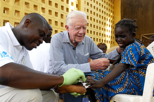Former U.S. President Jimmy Carter tries to comfort 6-year-old Ruhama Issah at Savelugu Hospital as a Carter Center technical assistant dresses Issah's extremely painful Guinea worm wound.