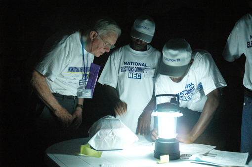 Preparing to count by lanternlight, former U.S. President Jimmy Carter observes poll closing procedures in Monrovia during Liberia's 2005 national elections.