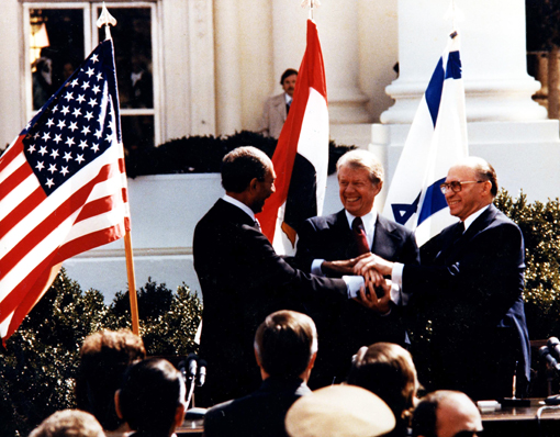 Egyptian President Anwar Sadat, U.S. President Jimmy Carter, and Israeli Prime Minister Menachem Begin make a three-way handshake at the signing of the Egyptian-Israeli Peace Treaty.