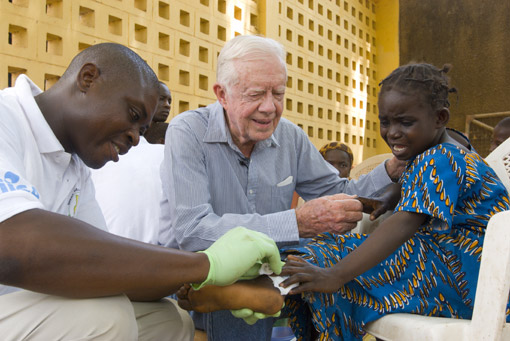 Former U.S. President Jimmy Carter comforts six-year-old Ruhama Issah as Adams Bawa, a Carter Center technical assistant, dresses her extremely painful Guinea worm wound.