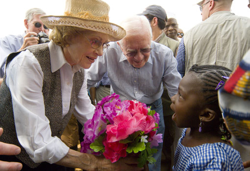 A young Nigerian girl presents former First Lady Rosalynn Carter with flowers.