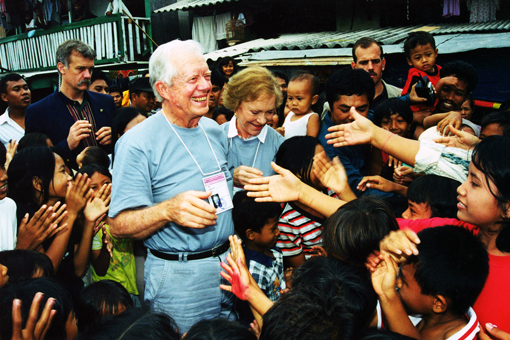 Former U.S. President Jimmy Carter and former First Lady Rosalynn Carter shaking hands with children during the Indonesian elections.