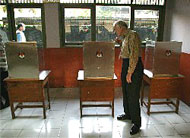 Former U.S. President Jimmy Carter examines a voting booth while poll workers finish setting up before voting begins in the July 5 Indonesia elections.