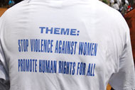 The back of a t-shirt reads Stop Violence Against Women, Promote Human Rights For All.