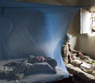 Photo of a bednet hung over a sleeping area and tucked under a mattress to protect sleepers from mosquitoes infected with malaria.