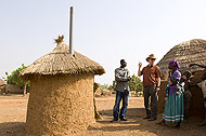 Photo of Dr. Paul Emerson, Nazeed Fusheini, and a Ghanain woman discussing her family's latrine.