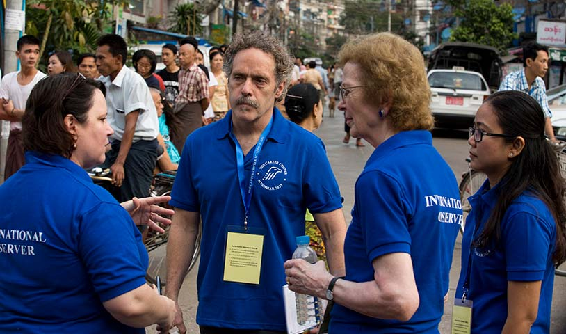 Photo of David Carroll with three observers, all in Carter Center branded blue t-shirts.