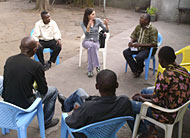 Valerie Hardin (top) joins a discussion with Father Gilbert Kalakumu and members of Church Saint Gonza.